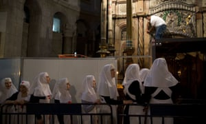 Christian nuns watch as a team of experts begin renovation of Christ's tomb in the Church of the Holy Sepulchre in Jerusalem.