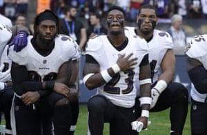 Tony Jefferson and Matt Judon of Baltimore Ravens kneel down with teammates in protest at US president Donald Trump as the American national anthem is played before the NFL football game against the Jacksonville Jaguars at Wembley Stadium