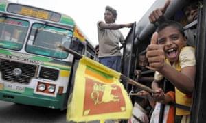 Boys wave the national flag in Colombo, Sri Lanka