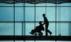 A silhouette of young man pushing old lady in a wheelchair.