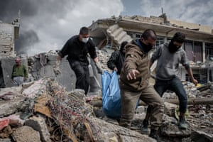 People carry a body recovered from the rubble of a house in western Mosul