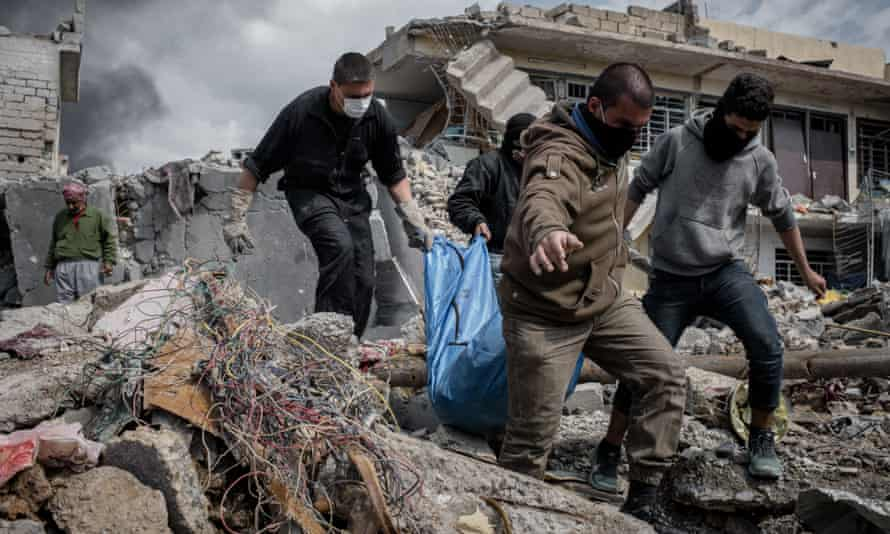 A rescue team recovers a body in Mosul after an airstrike.