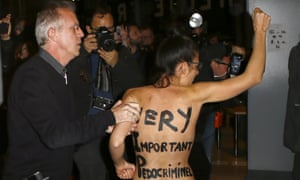 A Femen activist is led away by security staff member inside the film institute La Cinematheque Francaise in Paris