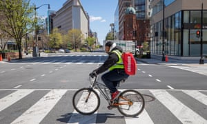 A Grubhub delivery person makes bicycle deliveries on the empty streets of Washington DC.