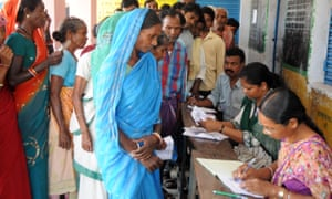 Indian residents waiting to vote queue to be processed by election officials at a polling station in 2014.