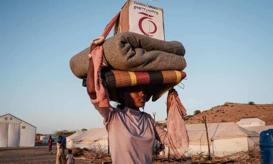 A woman at Um Raquba refugee camp in Gedaref, eastern Sudan, balancing matting, a blanket and a box on her head as she walks past white tents
