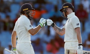 England's Jos Buttler, left, celebrates his half-century with Ben Stokes as the pair put on 124 runs for the fifth wicket in St Lucia.
