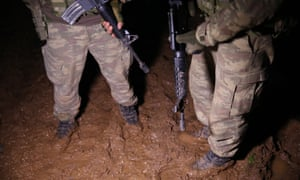 Syrian rebels patrol in muddy conditions in the Afrin region.