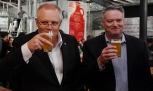 Scott Morrison and finance minister Mathias Cormann drink a beer to announce a budget tax cut on small kegs.
