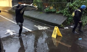 A person carrying a surfboard crosses a puddle