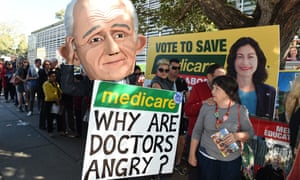 A protester wearing a giant puppet head of Malcolm Turnbull holds a sign criticising the government's policy on Medicare outside a polling booth in Brisbane on Saturday.