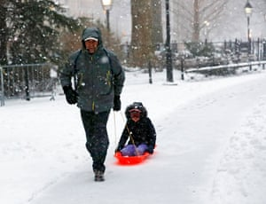A man pulls his child through the snow in Washington Square Park in New York City, where the schools were closed