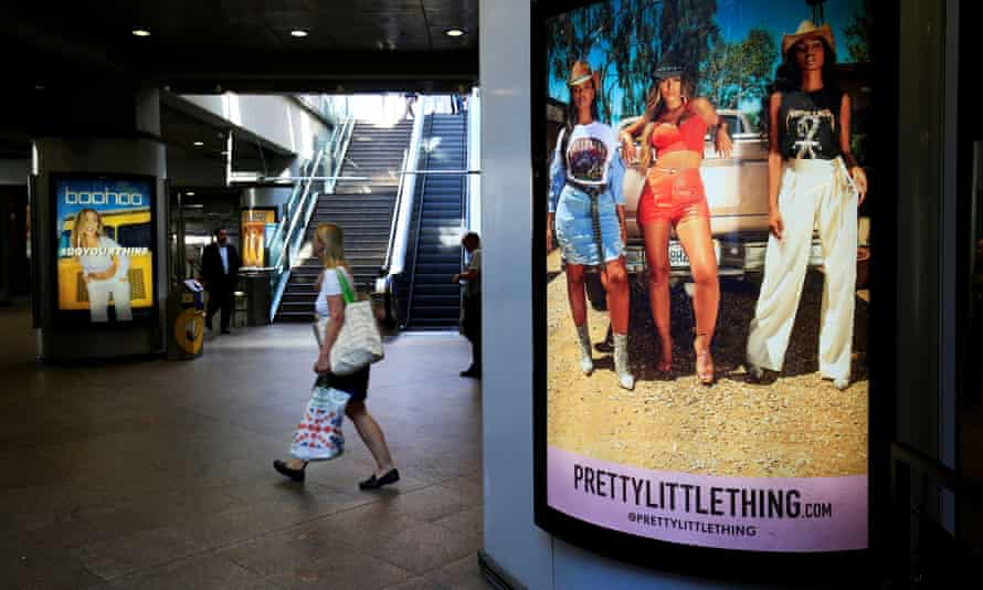 A shopper passes billboards for Boohoo and for Pretty Little Thing at Canary Wharf DLR station in London