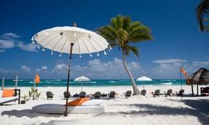 White umbrella behind a row of deckchairs on the beach at Shambala Petit Hotel, Mexico