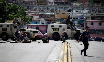 People pass by a street blocked by security forces during the strike in Caracas.