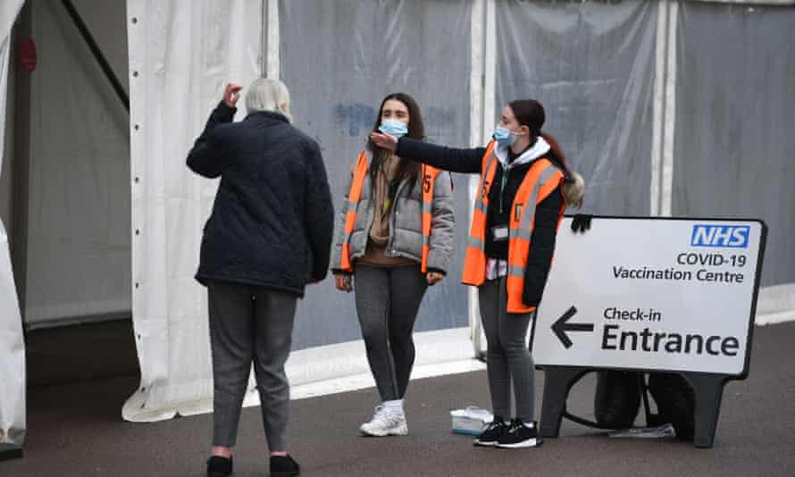 Volunteers direct a man into a temporary coronavirus vaccination facility in Colchester, Essex