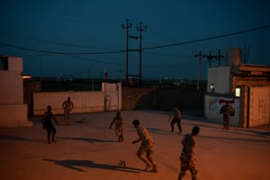 Iraqi army 20th division soldiers play soccer in a military base in Badoush, Iraq.