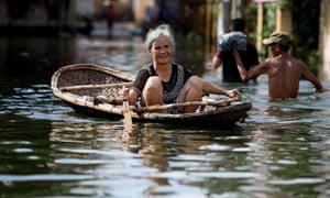 Hanoi, Vietnam: A woman rows a boat in a flooded area in Hanoi