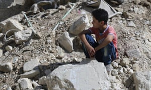 A boy sits amongst rubble in rebel-held eastern Aleppo, Syria.
