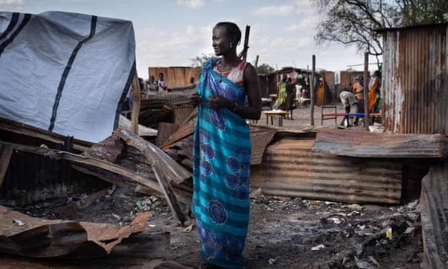 A woman stands at her burnt tea shop in a market in Gumuruk, South Sudan