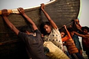 Rohingya refugees push a fishing boat from the sea at Shamlapur beach