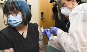 A nurse injects a volunteer with a vaccine candidate developed by the National Institutes of Health and Moderna in July.