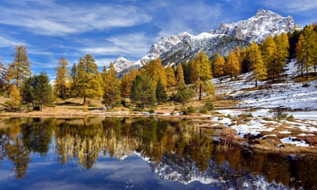 Snow-covered mountains and autumnal forest reflected in the Lai Nair, Tarasp, Switzerland.