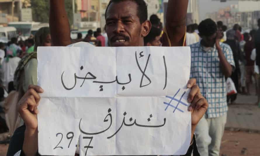 A man holds a placard saying 'El-Obeid is bleeding'