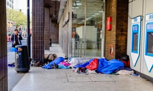 Homeless people sleep outside a station entrance in King's Cross, London.