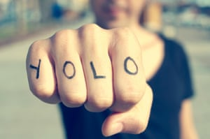closeup of a young man with the word yolo on his fist