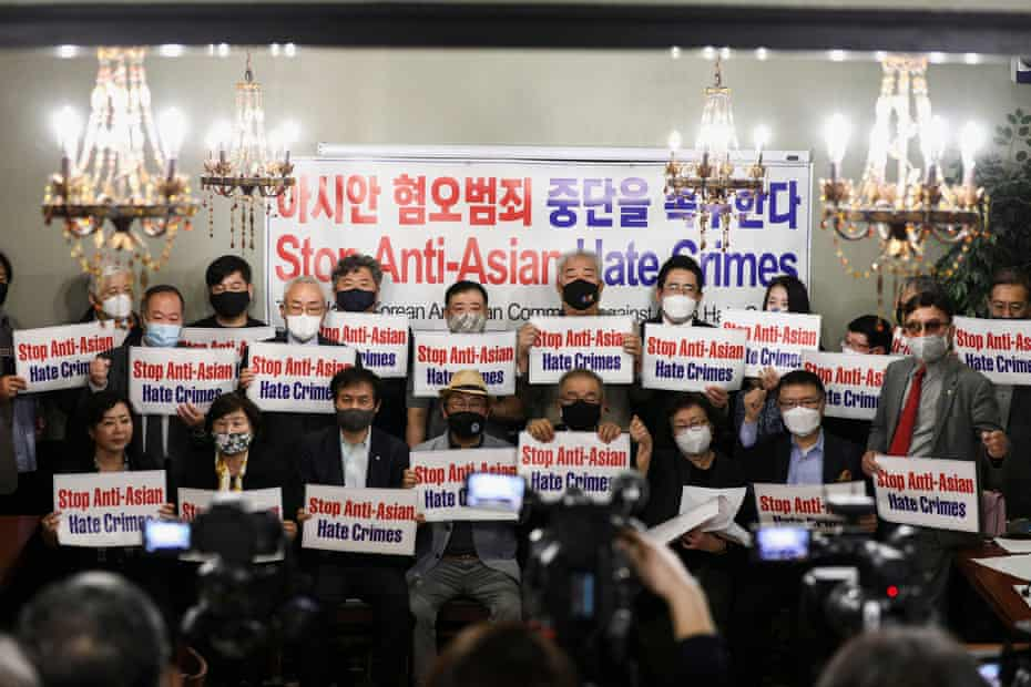 Members of the Atlanta Korean American Committee against Asian Hate Crime pose with placard safter the deadly shootings.