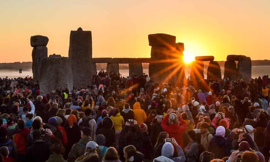 The sun rises between the stones and over crowds at Stonehenge on Friday