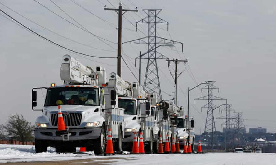 Electric utility trucks are parked in the snow in preparation of power outages due to weather in Fort Worth, Texas, this week.
