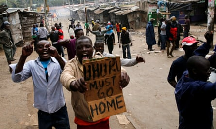 Protesters against Uhuru Kenyatta shout slogans and carry a banner in Mathare, Kenya