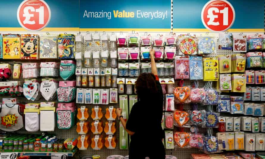 A Poundland employee checks products in a store in London