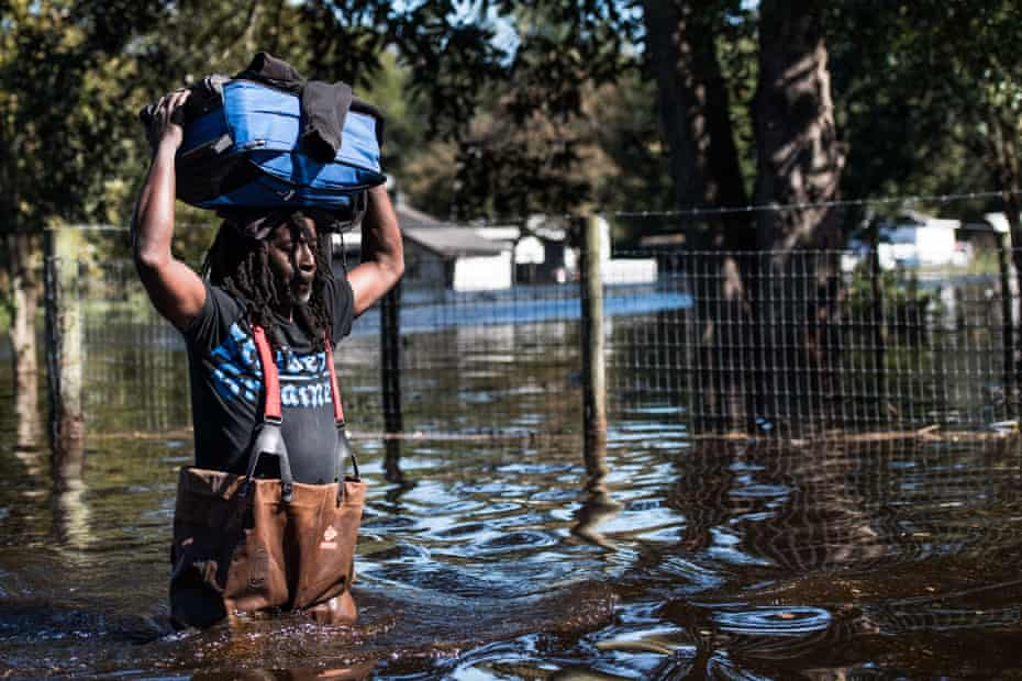 A man carries personal items through a flooded street caused by remnants of Hurricane Matthew on October 11, 2016 in Fair Bluff, North Carolina.