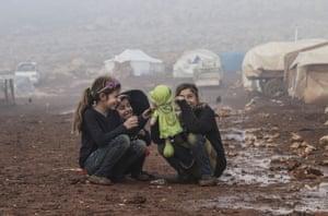 Idlib, Syria – Children play at a muddy refugee camp.