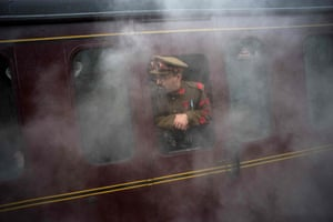 A steampunk enthusiast looks out from a steam train as it arrives at Haworth station
