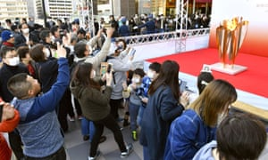 People gather to look at the Olympic flame on display in Sendai