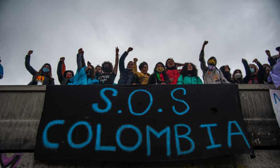 Protesters hang a sign on a bridge that reads 'SOS Colombia' in Bogotá on 5 May.
