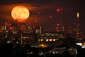 The full moon is seen rising above the London skyline, with the Shard skyscraper seen to the right