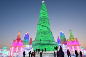People visit the ice sculptures illuminated by coloured lights at Harbin ice and snow world for the 34th Harbin International Ice and Snow Festival in Harbin city, China's northern Heilongjiang province, 04 January 2018.