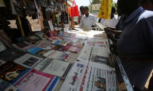 Sudanese men look at newspapers displayed at a kiosk in the capital Khartoum on February 16, 2015. Sudanese security officers seized the print runs of 14 newspapers in one of the most sweeping crackdowns on the press in recent years.