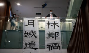 Pro-democracy lawmaker Cheuk Ting Lam hangs banners during a session of Hong Kong's Legislative Council on Thursday.