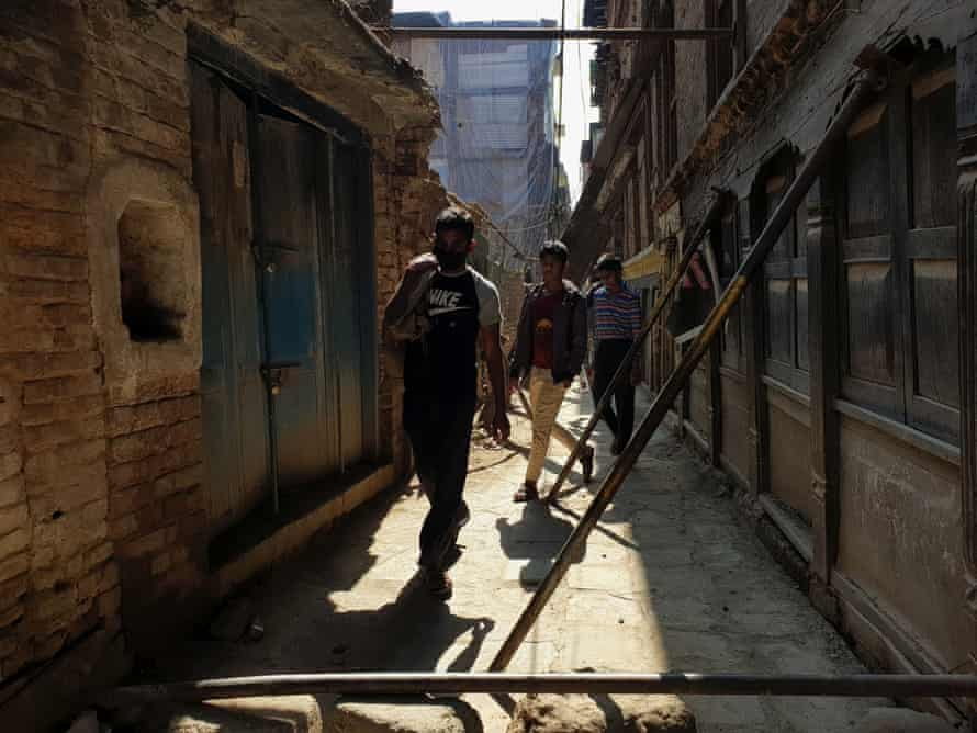 People walk in between iron planks kept in support for houses damaged during massive earthquake 2015 at an alley in Kathmandu