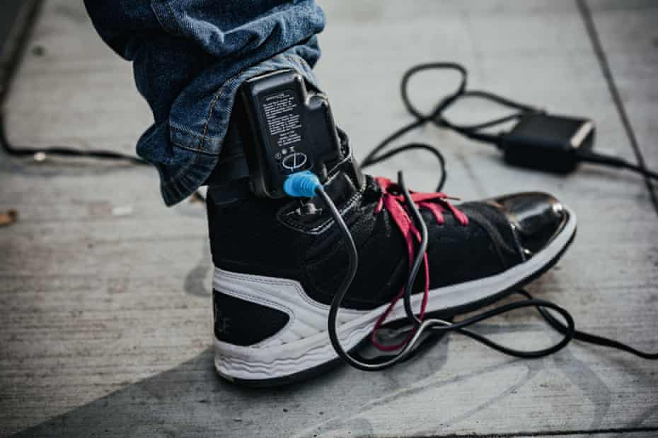 A close-up view of an ankle monitor, which needs to be charged for hours every day.