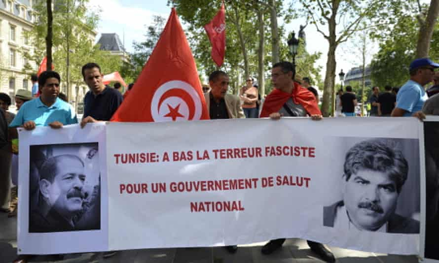Protesters hold a banner reading 'Tunisia: Down with fascist terror'.