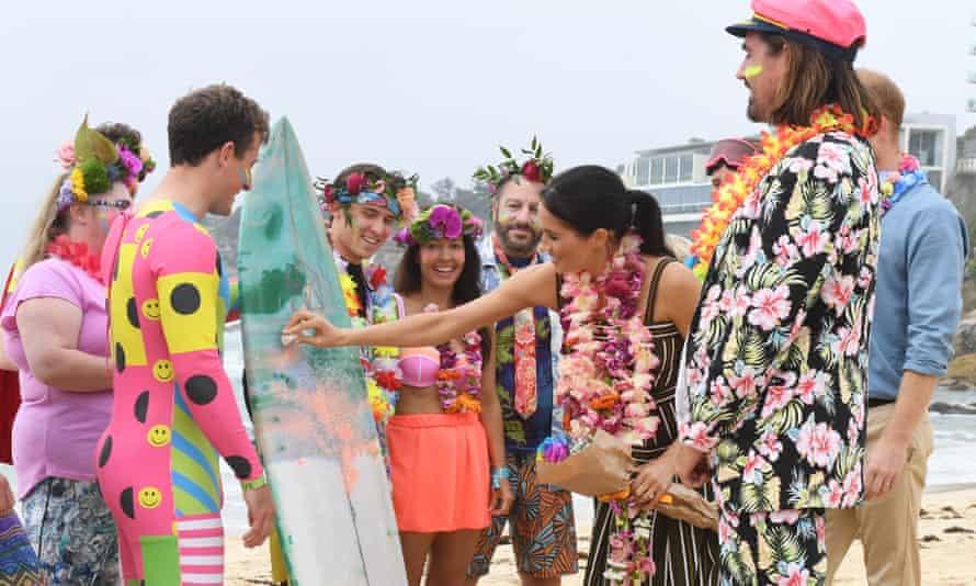 Meghan waxes a surfboard