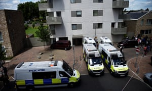 Officers and vehicles stand outside a block of flats that was raided by police in Barking, east London.