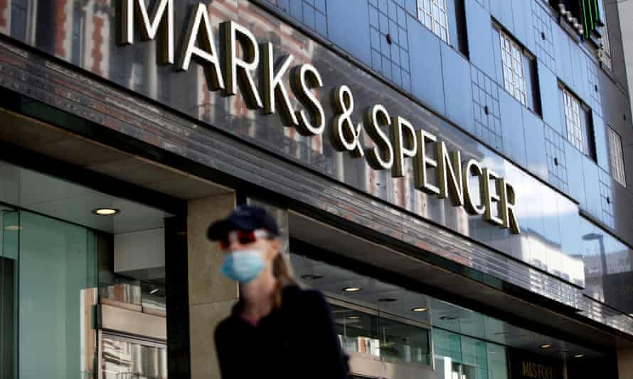 woman in mask walks past marks and spencer store